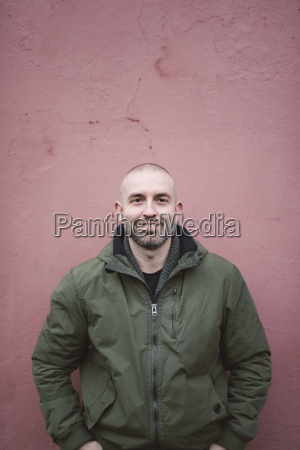 portrait of smiling bald man standing