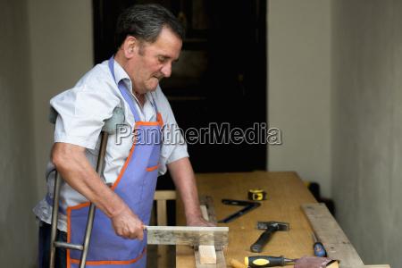 senior man with crutch sawing piece
