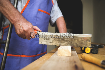 man with crutch sawing piece of