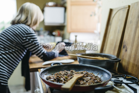 woman using digital tablet while cooking