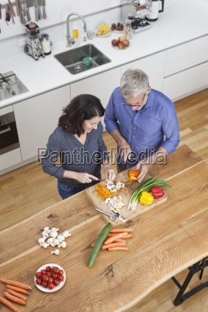 mature couple preparing vegetables in kitchen