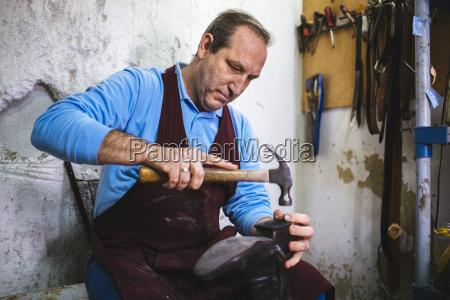 shoemaker repairing a shoe in his