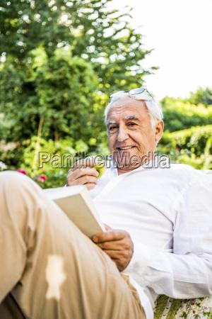 smiling senior man reading book in