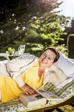 smiling mature woman reading book on
