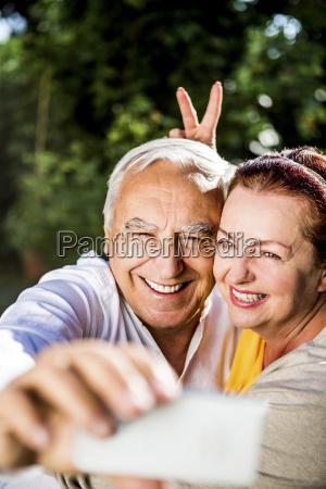 playful elderly couple taking a selfie