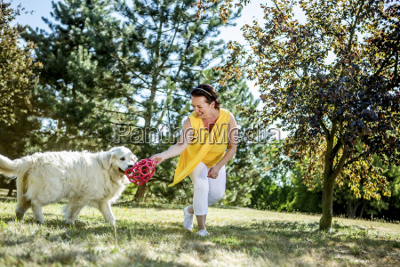 mature woman playing with dog on