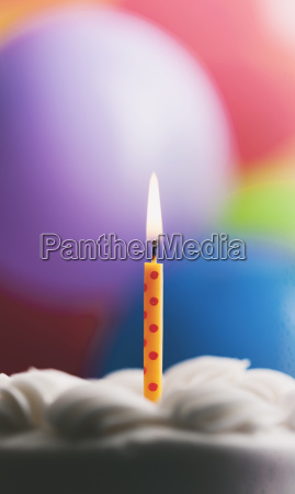 lighted birthday candle on a cake