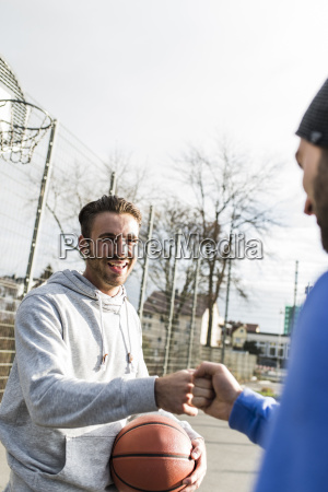 two young basketball players greeting