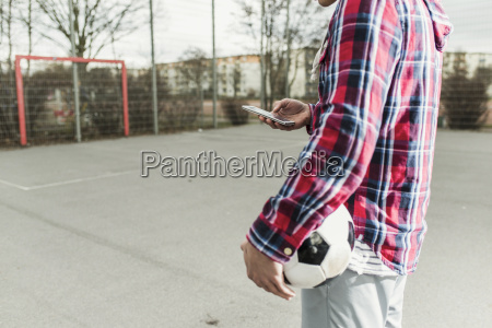 young football player with smartphone
