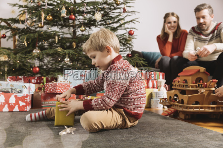 little boy opening christmas gift with