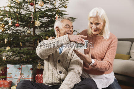 senior couple exchanging christmas gifts in