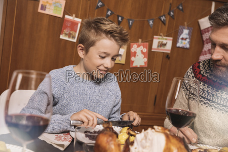 father and son having christmas dinner