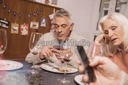 annoyed senior woman with husband using