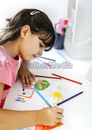 little girl drawing on his desk
