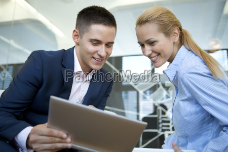 smiling businessman and businesswoman looking at