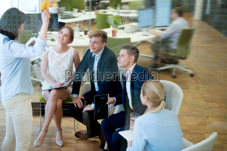 businesswoman talking to expectant businessspeople in