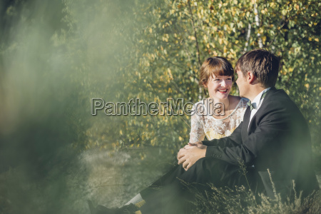 happy bridal couple sitting face to