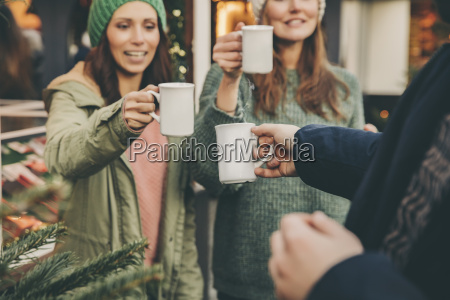 happy friends clinking cups of hot