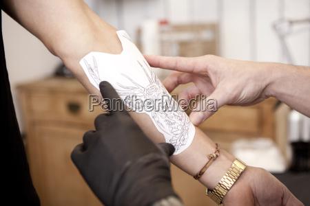 hands of tattooist attaching stencil on
