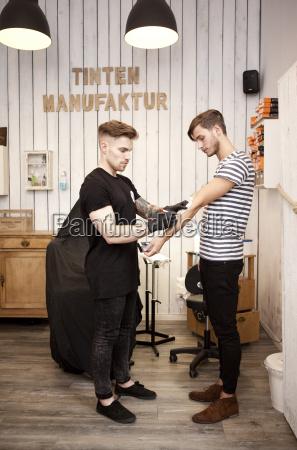 tattooist attaching stencil on forearm of
