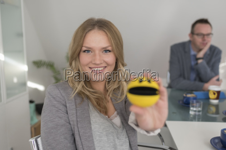 smiling woman holding smiley face in
