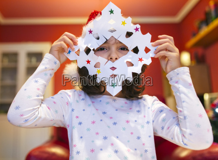 little girl with tinkered christmas decoration