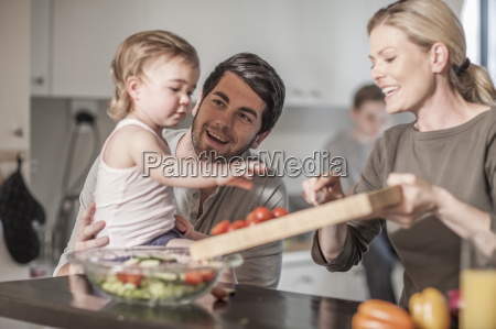 family in kitchen preparing food together