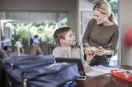 mother handing fruit salad to son
