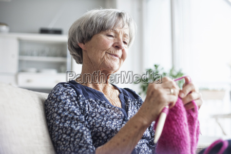 portrait of knitting senior woman sitting