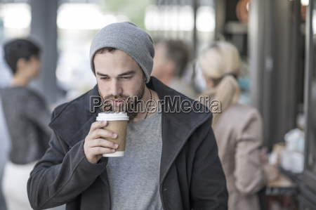 young man drinking takeaway coffee in