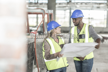 woman and construction worker discussing construction