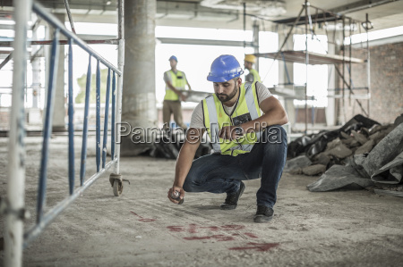 construction worker spaying marks on floor