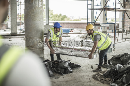 two construction workers carrying item in