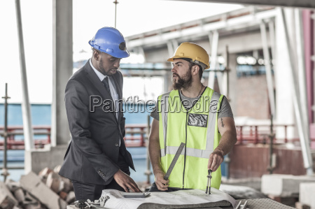 construction worker and businessman discussing on
