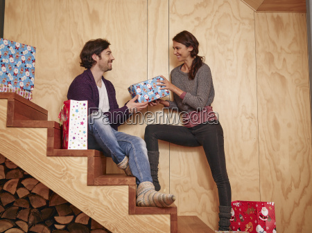 happy couple sitting on wooden stairs