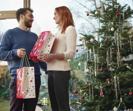 couple standing in front of christmas