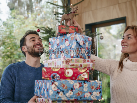 man carrying stack of christmas presents