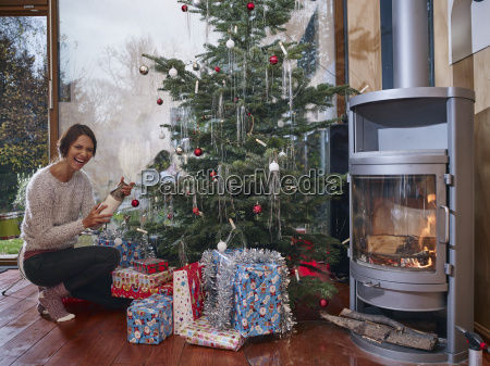 woman unwrapping christmas gifts under christmas