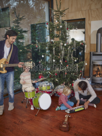family playing music together under christmas