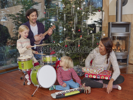 father and daughters playing music on