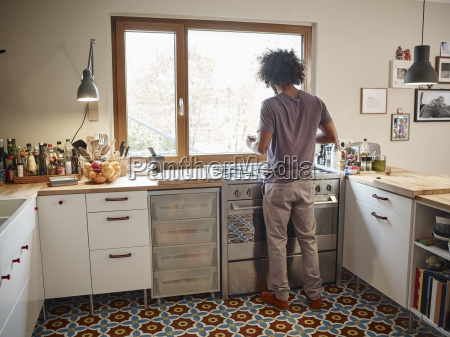 young man standing at stove in