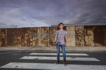 boy holding his skateboard standing on