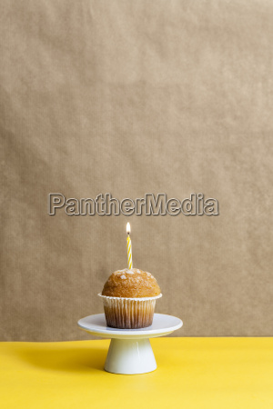 muffin with lighted candle on a