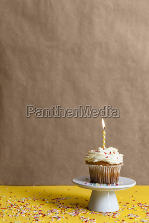cup cake with lighted candle sprinkled