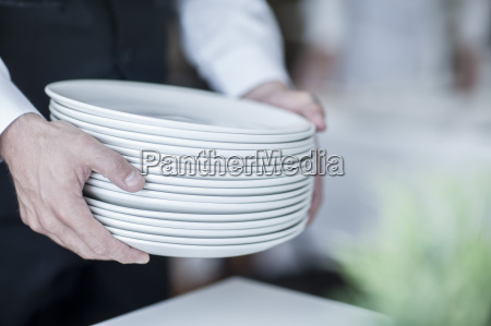 waiter carrying stack of plates close