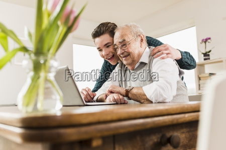 senior man and his grandson looking