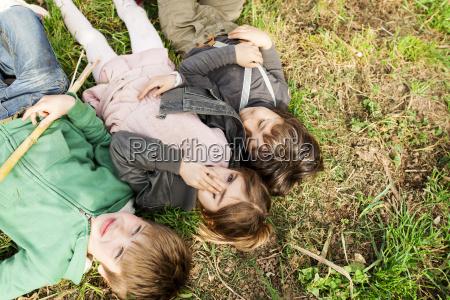 three kids lying in grass