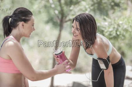 two sportswomen sharing water after running