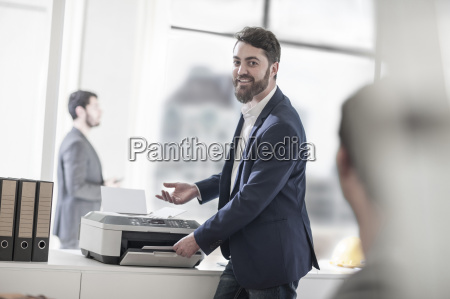 smiling man in office using printer