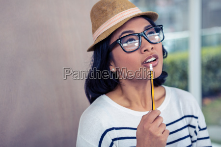 thoughtful asian woman with pencil on